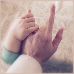 """Baby hand holding mom hand signing """"I love you"""""""