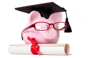 A pink piggy bank wearing glasses and a ceremonial graduation cap stands next to a diploma with a red tie.