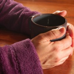Two hands cupping a mug of tea