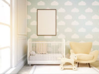 Close up of child's room with a vertical framed poster, a cradle, an armchair and a toy horse. There is a large window and light blue cloud wallpaper. 3d rendering. Mock up. Toned image