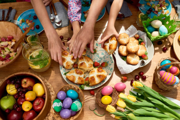 High angle view of family taking sweet buns when they having Easter dinner together