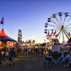 St. Paul, Minnesota, USA - August 30, 2016: Minnesota State Fair Midway Farris Wheel and Game Stands at Dusk. The Midway is full of rides and food. The Minnesota State Fairs runs from August 25th to September 5th in 2016.