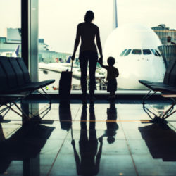 A picture of a woman and her little boy standing holding hands with their suitcase in a waiting area lobby at the Frankfurt airport, a large plane visible through the big bay windows.  High contrast leaves just their silhouettes visible.  Meant to depict travel with a child or infant.  Horizontal image.