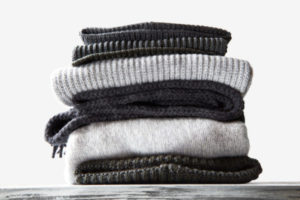 stacked black and grey knitted sweaters on a white background