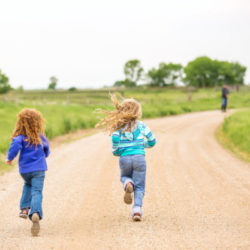 Rear view of two young girls (sisters) running down a rural gravel driveway. The younger sister is on the left and has curly red hair. The older sister is on the right and has curly blonde hair. Grandpa can be seen standing up ahead of them in the distance waiting for them to catch up.