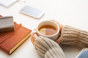 Close up of woman hands holding a cup of lemon tea on white table in a winter afternoon. Woman hands holding hot drink on table. Female hands with beige warm sweater holding hot tea with a slice of lemon.