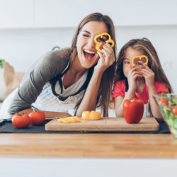 Mother and daughter having fun with the vegetables in the kitchen.