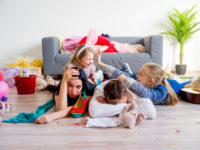 Tired parents lying on floor and their romping kids