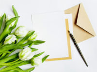 Letter, envelope and bunch of fresh tulips on white background. Vintage wedding invitation card or love letter with white flowers. Romantic or holiday concept, top view, flat lay, overhead view