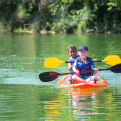 Two cute diverse young boys kayaking down a beautiful river. Smiling and having fun together on a warm day at summer camp