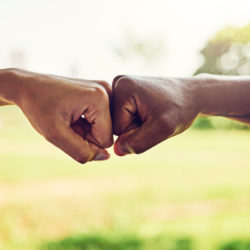 Closeup shot of two unrecognizable people fist bumping outdoors