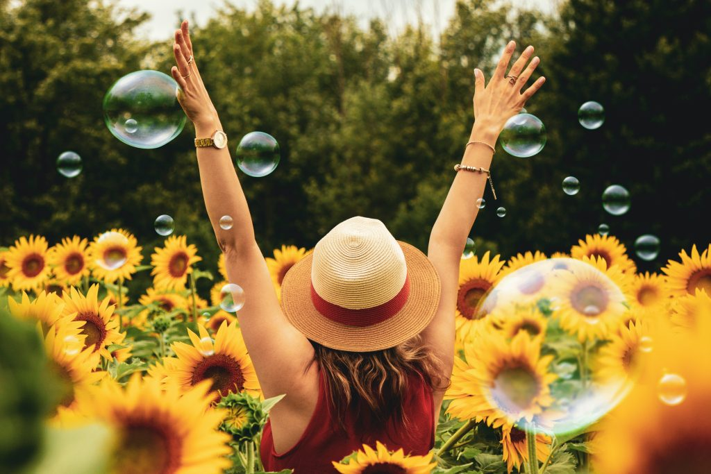 A mom's guide to summer - Mom wearing a hat and dress in a sunflower field with hands raised in the air.