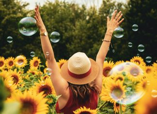 Woman standing in sunflower field facing away from the camera with hands raised in the air.