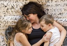 brunette mom snuggling toddler son and daughter in bed