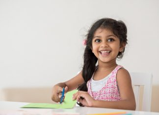 little girl cutting paper at a table