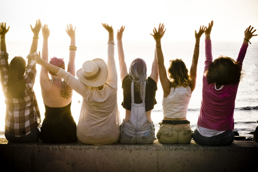 rear view of group of diverse females friends enjoying at the sunset with ocean in background - why friendship matters