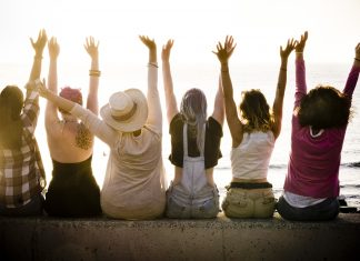 rear view of group of females caucasian friends enjoying at the sunset with ocean in background - success and satisfaction concept for nice people together with joy - friendship and vacation
