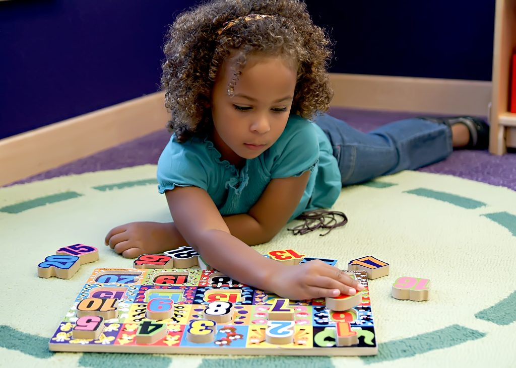 young preschool girl works on a numbers puzzles executive function