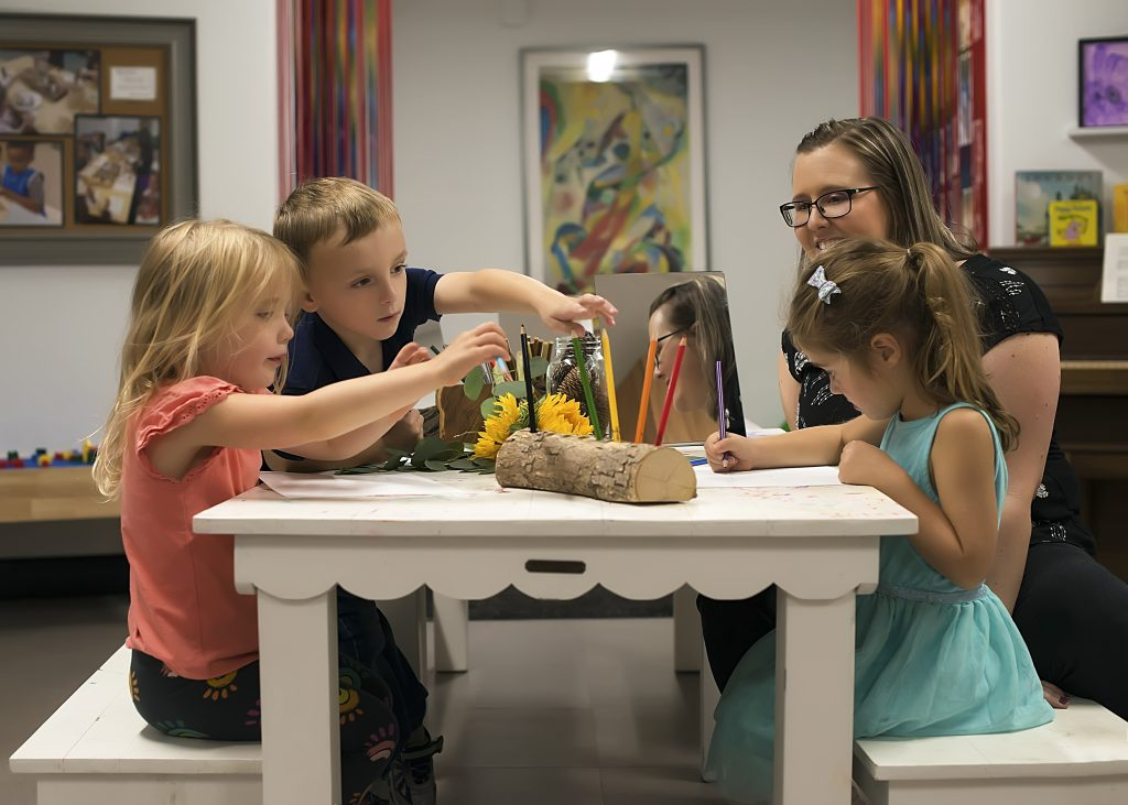 teacher works with two girls and one boy at a small classroom table - executive function