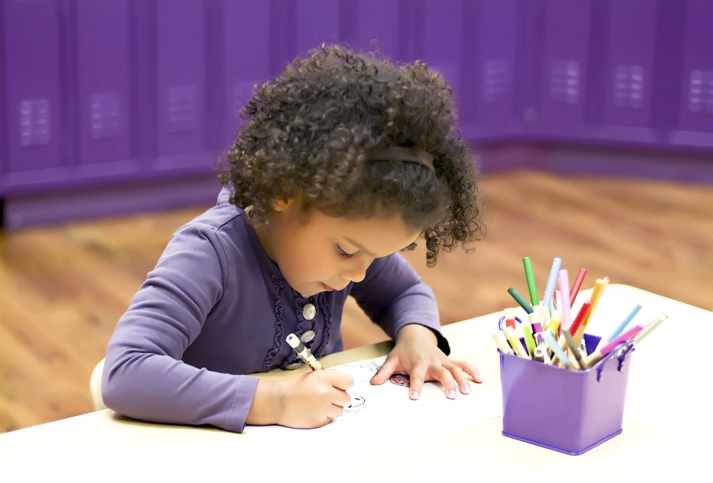 Young child working on coloring at a table - Executive Function Skills Kinderberry Hill