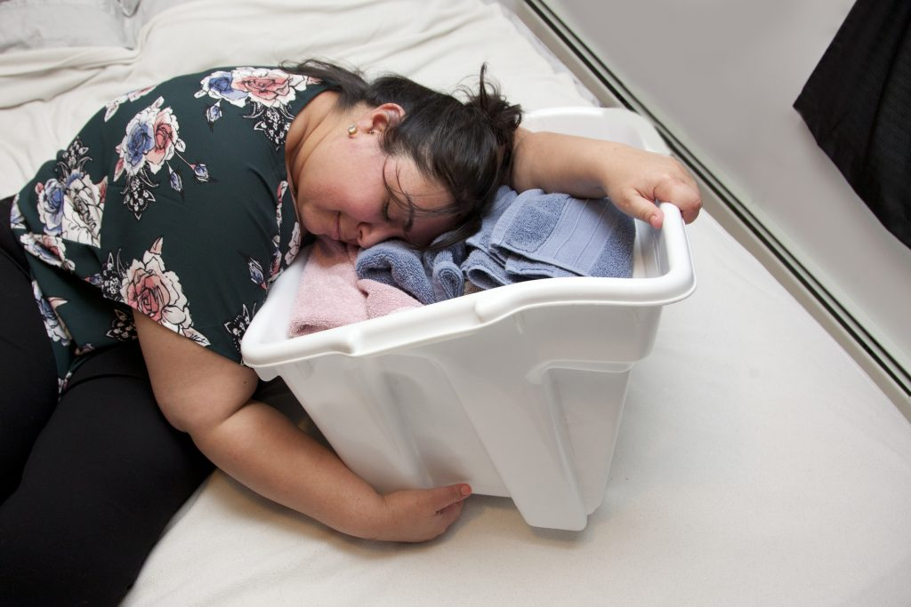 Tired mom asleep in her laundry basket