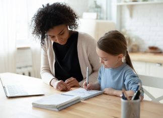 Stepmother helps stepdaughter with her homework. Managing back to school between two homes.