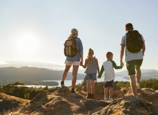 Travel with kids - rear view of mother, father and two children at the top of a hill overlooking a lake