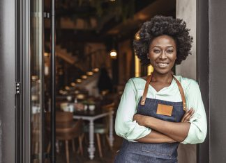 Comcast RISE Cheerful female café owner standing at the door with her arms crossed. African woman in apron standing with her arms crossed