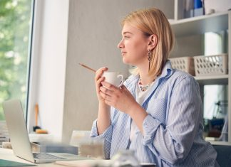 Blonde woman at desk having coffee. Going back in the office