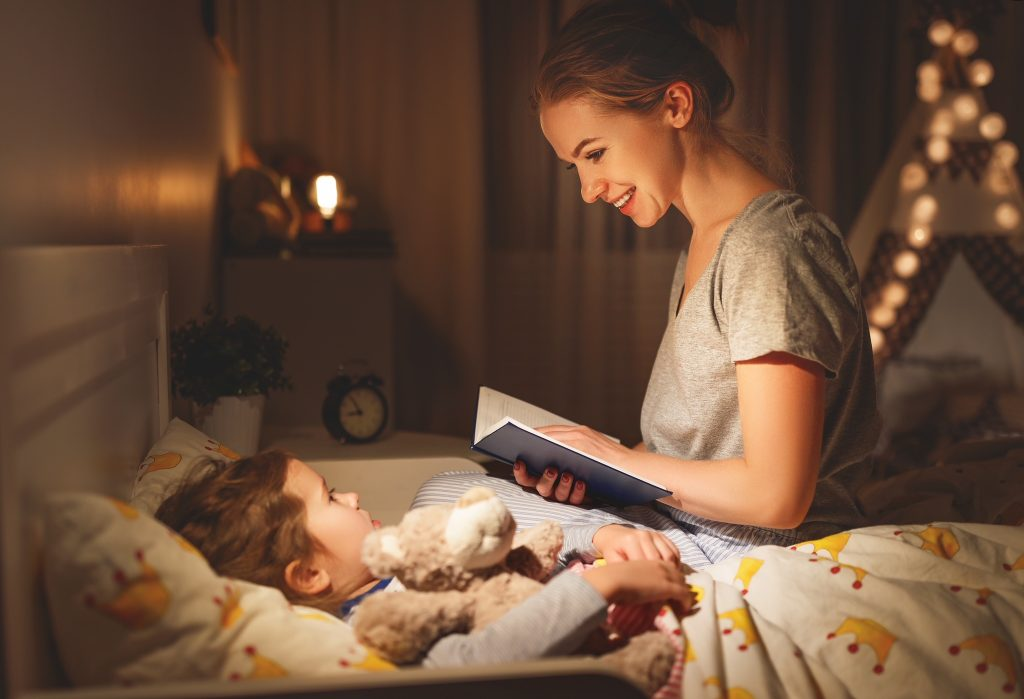 Children Health and Wellness. mother and child daughter reading book in bed before going to sleep