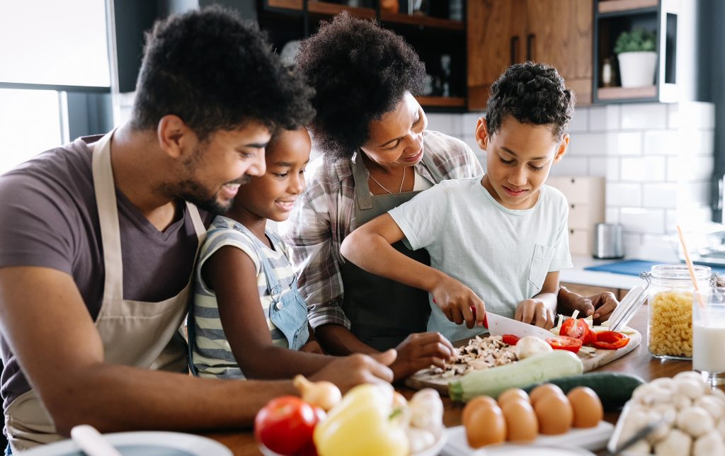 Children Health and Wellness Happy black family in the kitchen having fun and cooking together: