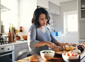 Shot of an attractive young woman cooking at home. Support your immune system