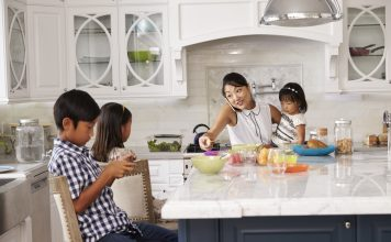 juggle it all: Busy Mother Organizing Children At Breakfast In Kitchen