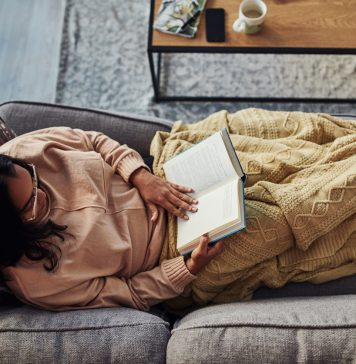 Practicing Self Care - High angle shot of a young woman reading a book on the sofa at home