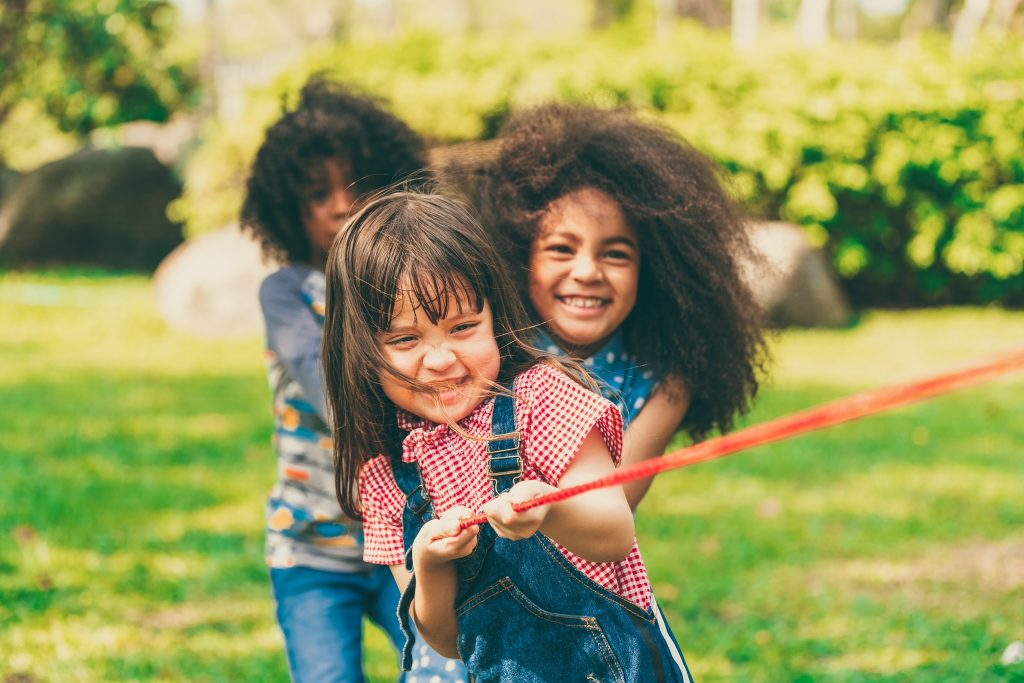 Children Health and Wellness. Happy children playing tug of war and having fun during summer camping in the park. Children recreation concept.