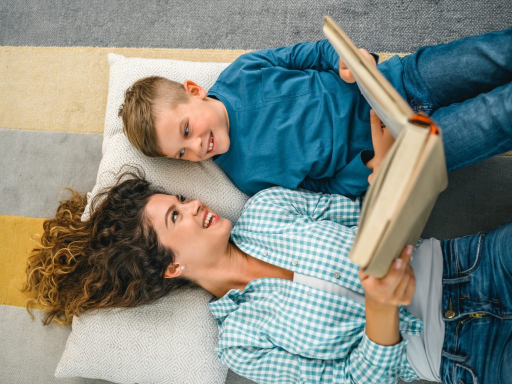 3 steps to chapter books Little boy and mother enjoying book together.