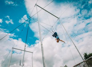kid having swing on a high flying trapeze,