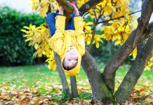 Let them be little - Little boy in a yellow raincoat hanging on a tree branch